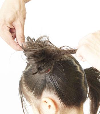 4.穴に通した毛束を二つに分け、きゅっと締めます。
