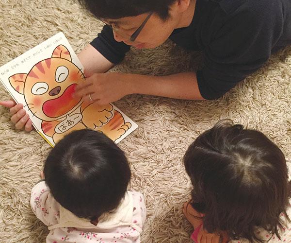 2人の子供に絵本を読み聞かせる笠原氏。